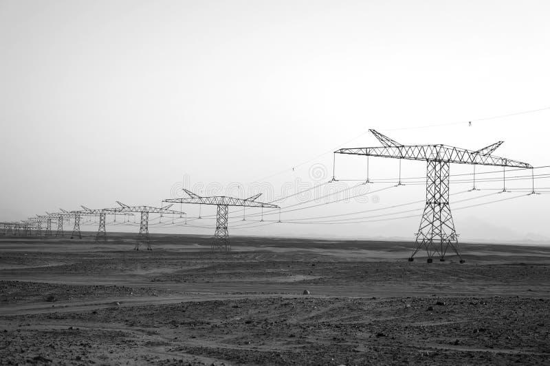 Electricity pylons in sand desert stock photos