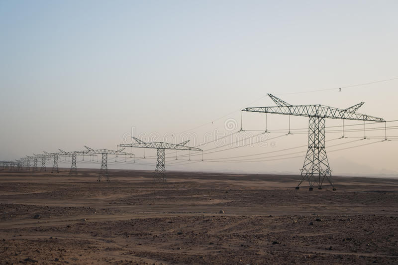 Electricity pylons in sand desert stock images