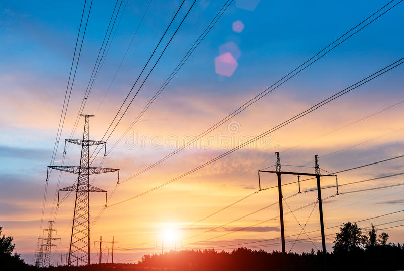Electricity transmission pylon silhouetted against blue sky. high voltage post. stock photography