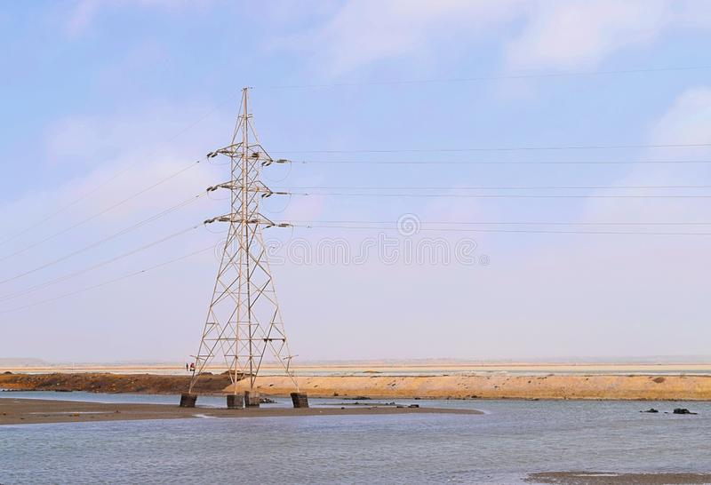 Electricity Transmission Tower with Overhead High-Voltage Power Line Surrounded by Water in Flood - stock photo