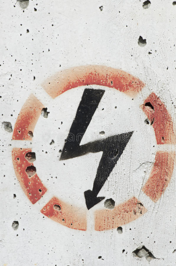 Electricity warning sign. Painted on a concrete wall royalty free stock photo