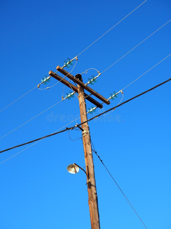 Electricity Wires and Pole. A wooden power pole, made from a single pine tree trunk, with domestic electricity supply wires and telephone and data wires., with royalty free stock photos