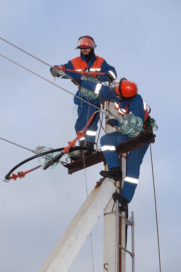 Electrics δύο που λειτουργεί πάνω από έναν πυλώνα ηλεκτρικής ενέργειας στοκ εικόνες