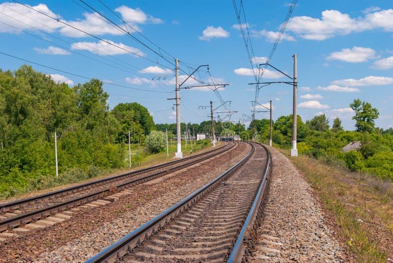 Electrified двухпутная железная дорога в России на солнечный день стоковое изображение