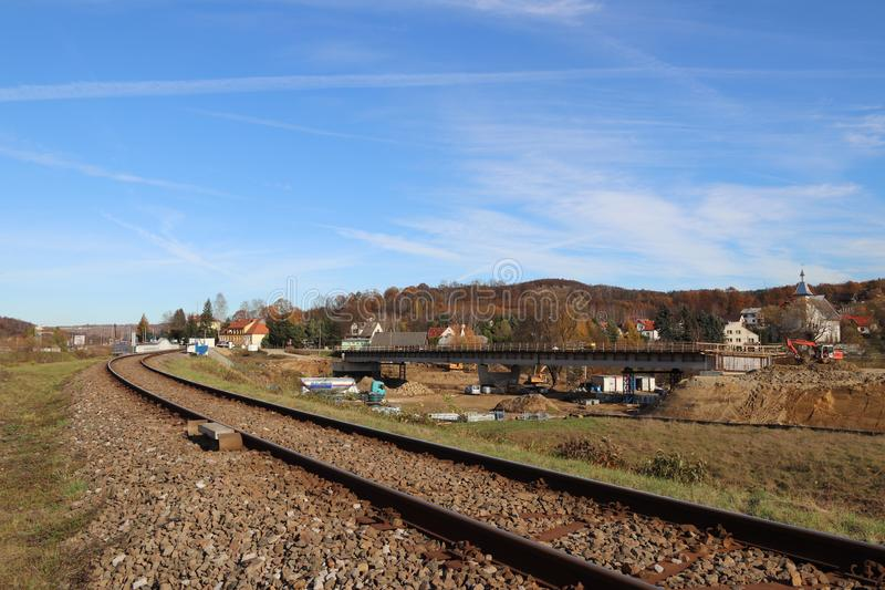 Electrified железнодорожный путь среди зеленых лугов и пшеничных полей Строить мост в маленьком городе стоковые фото