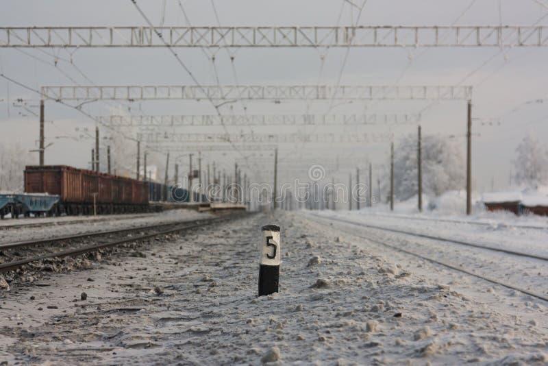 Electrified железнодорожные пути - и железнодорожный вокзал с знаком уличного движения в зиме стоковые фото
