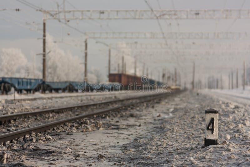 Electrified железнодорожные пути - и железнодорожный вокзал с знаком уличного движения в зиме стоковые изображения rf