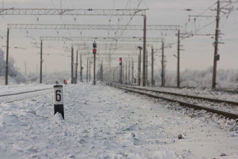 Electrified железнодорожные пути с красными железнодорожными сигналами - железнодорожным вокзалом с знаком уличного движения в зи стоковая фотография