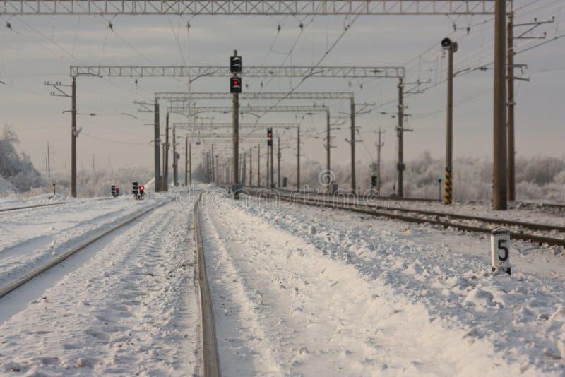 Electrified железнодорожные пути с красными железнодорожными сигналами - железнодорожным вокзалом с знаком уличного движения в зи стоковые изображения rf