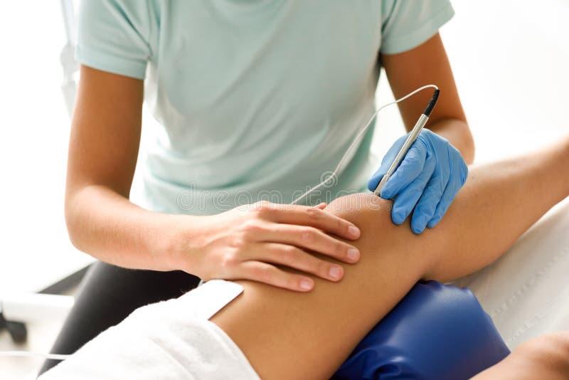 Electroacupuncture trocken mit Nadel auf weiblichem Knie lizenzfreie stockfotografie