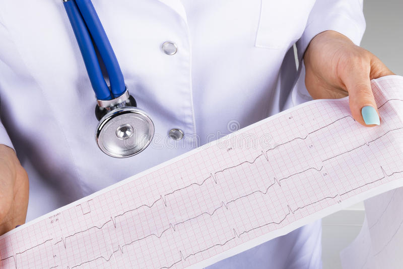 Electrocardiogram, ecg in hand of a female doctor. Medical health care. Clinic cardiology heart rhythm and pulse test closeup. stock photo