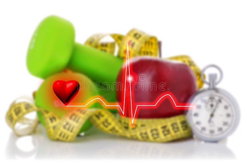 Electrocardiograma en el fondo de pesas de gimnasia, forma de vida sana roja del concepto de la manzana y de la cinta métrica fotografía de archivo libre de regalías