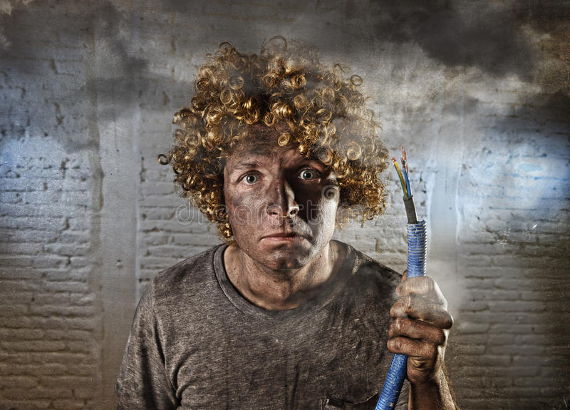 Electrocuted man with cable smoking after domestic accident with dirty burnt face shock electrocuted expression. Young man electrocuted with funny curly wig royalty free stock photo