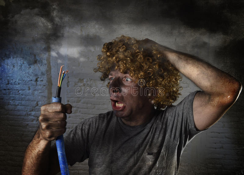 Electrocuted man with cable smoking after domestic accident with dirty burnt face shock electrocuted expression. Young man electrocuted with funny curly wig stock image