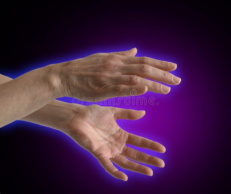Electromagnetic Aura around healer's hands. Blue Electromagnetic Aura around healer's hands on a dark purple background royalty free stock images