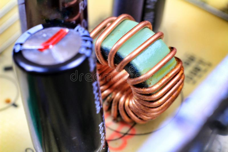 Electromagnetic coil and Capacitors in an electronic board. Alicante, Spain- May 7, 2019: Macro photography of Electromagnetic coil, capacitors and other stock image