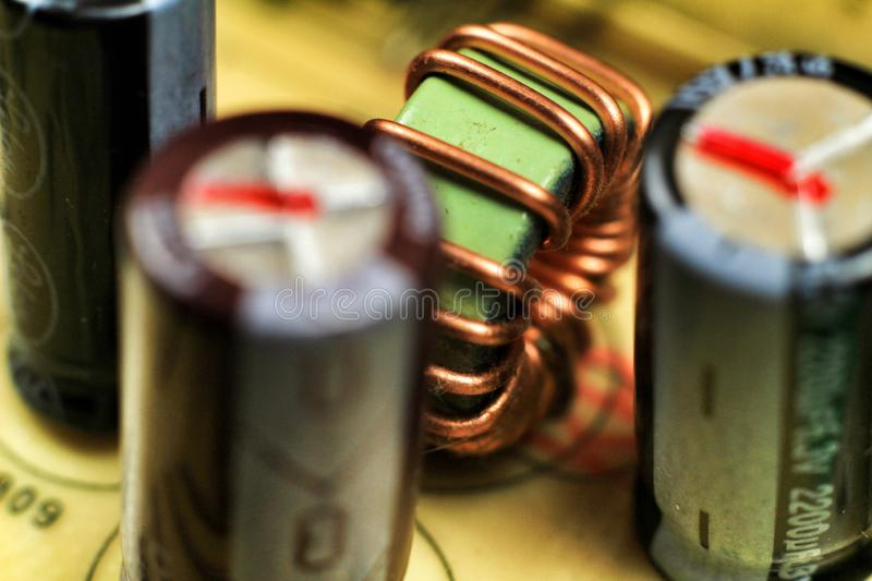 Electromagnetic coil and Capacitors in an electronic board. Macro photography of Electromagnetic coil, capacitors and other electronic components in an stock photo