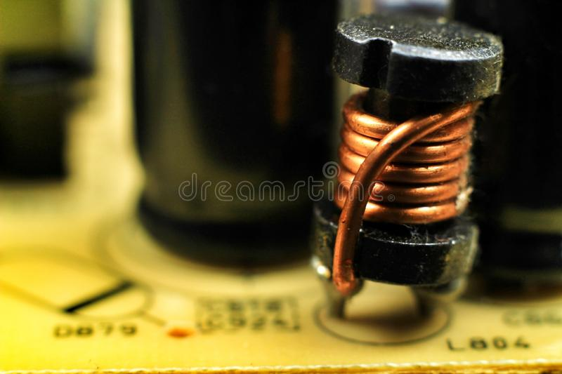 Electromagnetic coil on a motherboard. Closeup of and electromagnetic coil on a motherboard electric detail wound metal induction current electrical neat choke royalty free stock images