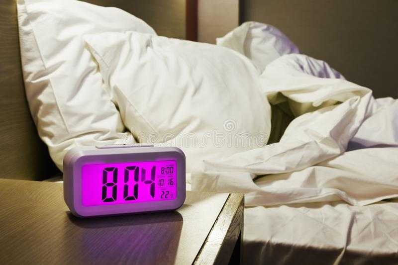 Electronic alarm clock stands on a bedside table. In the room or hotel room royalty free stock photos