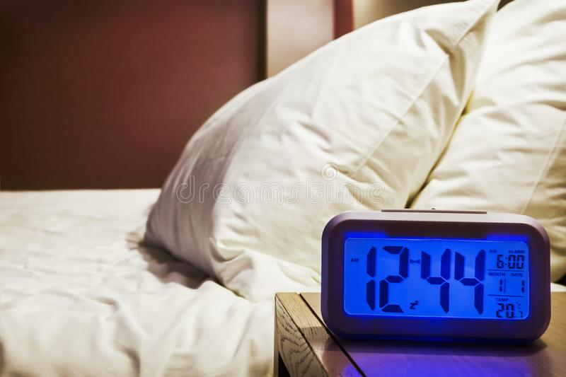 Electronic alarm clock stands on a bedside table. In the room or hotel room royalty free stock images