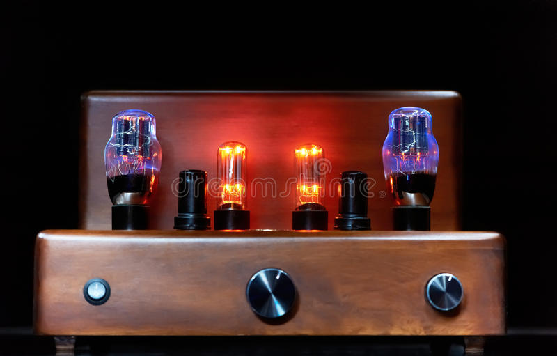 Electronic amplifier with glowing bulb lamp stock image