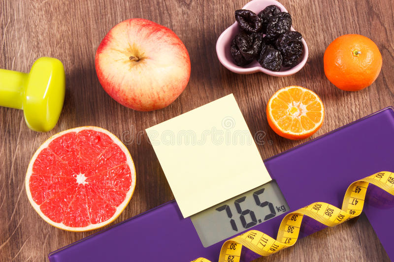 Electronic bathroom scale, centimeter, healthy food, dumbbells for fitness, slimming and healthy lifestyles concept. Electronic bathroom scale with result of stock photos