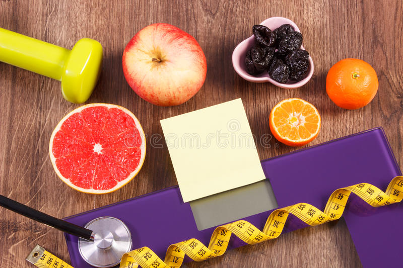 Electronic bathroom scale, centimeter and healthy food, slimming and healthy lifestyles concept. Electronic bathroom scale for weight of human body, tape measure royalty free stock photos