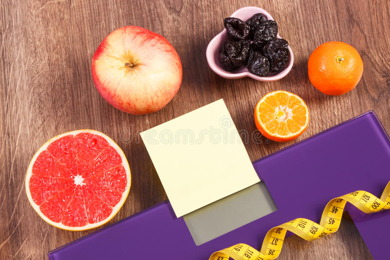 Electronic bathroom scale, centimeter and healthy food, slimming and healthy lifestyles concept. Electronic bathroom scale for weight of human body, tape measure royalty free stock photo