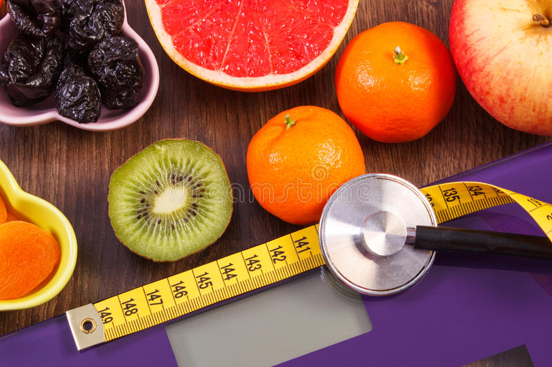Electronic bathroom scale, centimeter and stethoscope, healthy food, slimming and healthy lifestyles concept. Digital electronic bathroom scale for weight of royalty free stock image