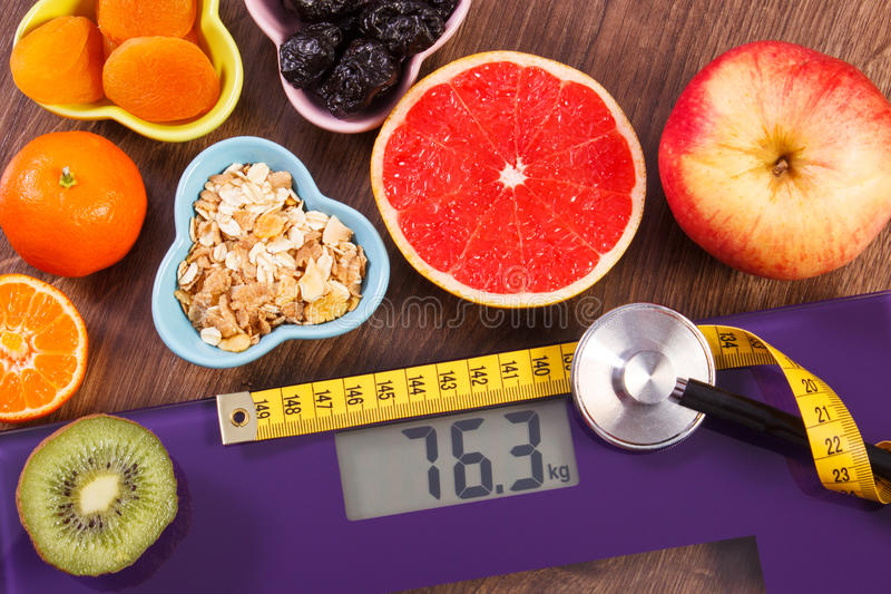 Electronic bathroom scale, centimeter and stethoscope, healthy food, slimming and healthy lifestyles concept. Digital electronic bathroom scale for weight of stock image