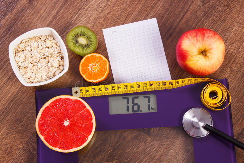 Electronic bathroom scale, centimeter and stethoscope, healthy food, slimming and healthy lifestyles concept. Electronic bathroom scale for weight of human body royalty free stock image