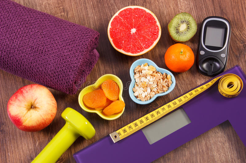 Electronic bathroom scale, glucometer, centimeter, healthy food and dumbbells for fitness, healthy lifestyles, diabetes and. Electronic bathroom scale for weight royalty free stock photos