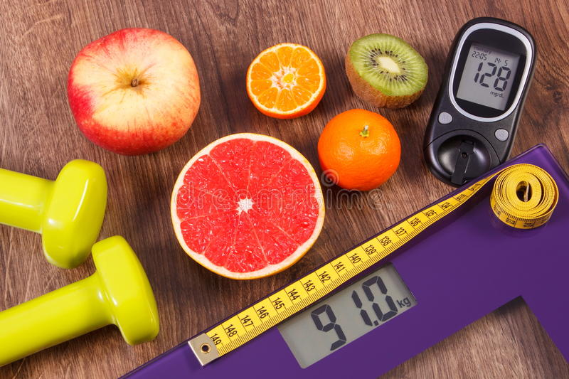 Electronic bathroom scale and glucometer with result of measurement, centimeter, healthy food and dumbbells, healthy lifestyles. Electronic bathroom scale and royalty free stock images