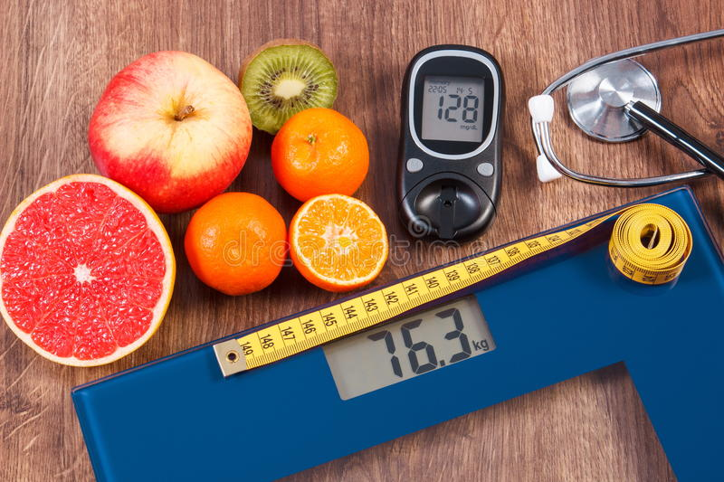 Electronic bathroom scale and glucometer with result of measurement, centimeter, stethoscope and healthy food, healthy. Electronic bathroom scale and glucose royalty free stock images