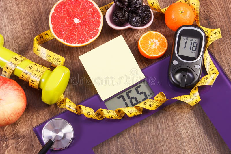 Electronic bathroom scale and glucometer with result of measurement, healthy food and dumbbells, healthy lifestyles, diabetes and. Electronic bathroom scale and stock photo