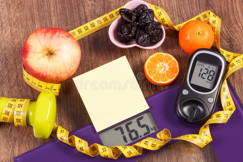 Electronic bathroom scale and glucometer with result of measurement, healthy food and dumbbells, healthy lifestyles, diabetes and. Electronic bathroom scale and stock image