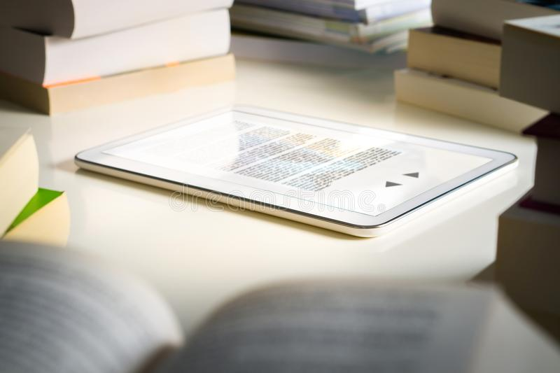 Electronic book reader. Modern smart device for reading. Electronic book reader. Modern smart device for reading surrounded by stacks of traditional books stock photos