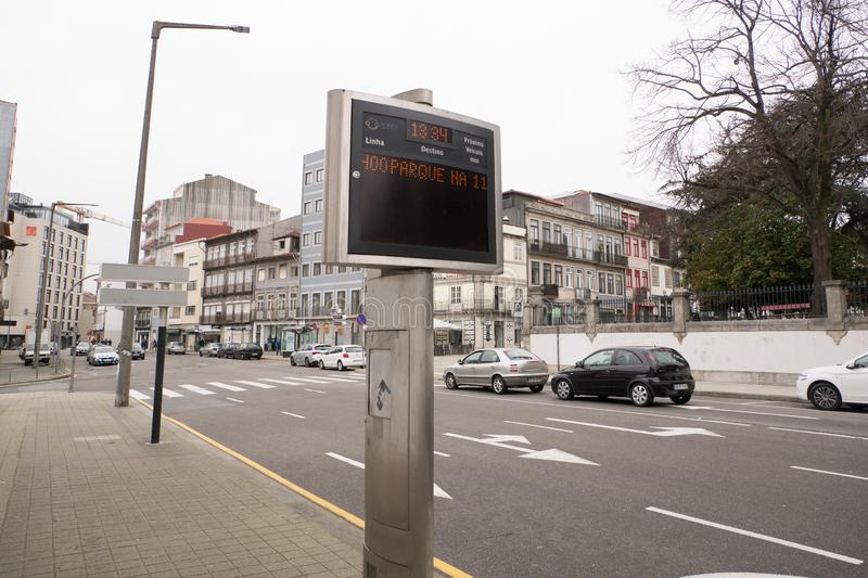 Traditional Portuguese architecture with stone door frames in a dark street in Porto, PortugalElectronic bus stop sign in the stre. Electronic bus stop sign in royalty free stock images