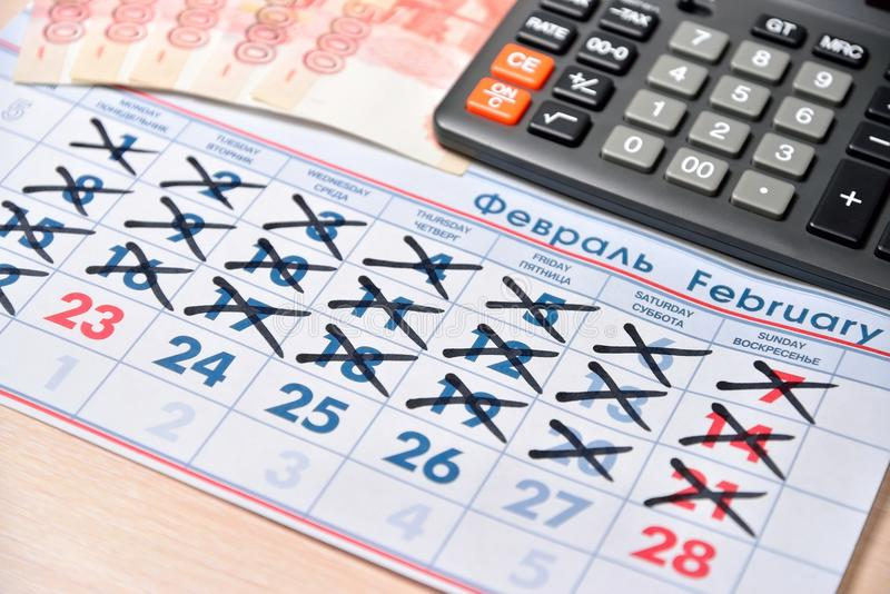 Electronic calculator, banknotes of five thousand rubles, calendar with holidays day on February 23 are on the table. Business still life royalty free stock image