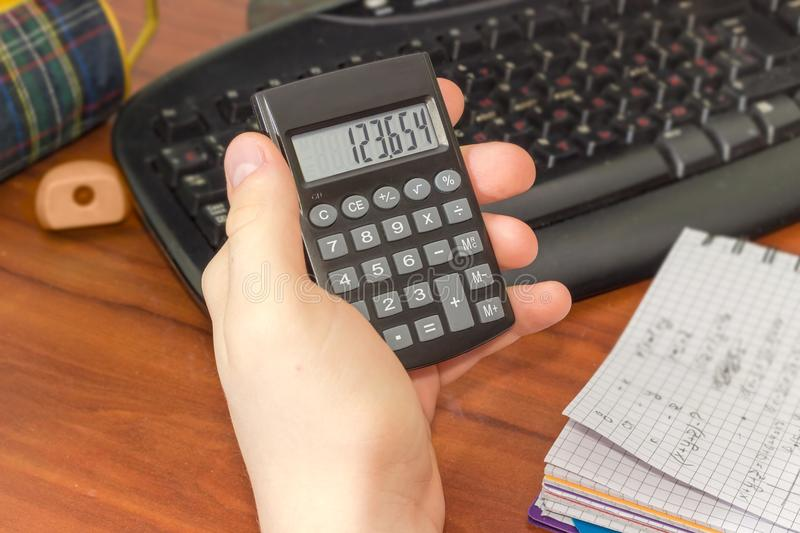 Electronic calculator in the hand of schoolboy over the desktop. Modern electronic pocket calculator with a liquid-crystal display in the hand of schoolboy on a royalty free stock images