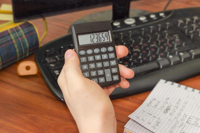 Electronic calculator in the hand of schoolboy over the desktop. Modern electronic pocket calculator with a liquid-crystal display in the hand of schoolboy over royalty free stock image