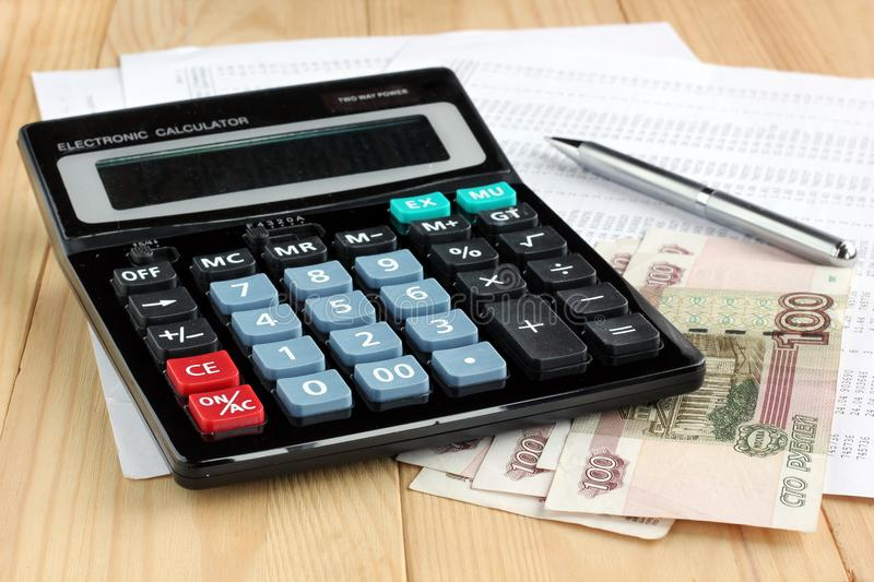 Electronic calculator, pen and Russian money on sheets of paper. Electronic calculator, metal pen and Russian money on sheets of paper with numbers. Finance royalty free stock photo