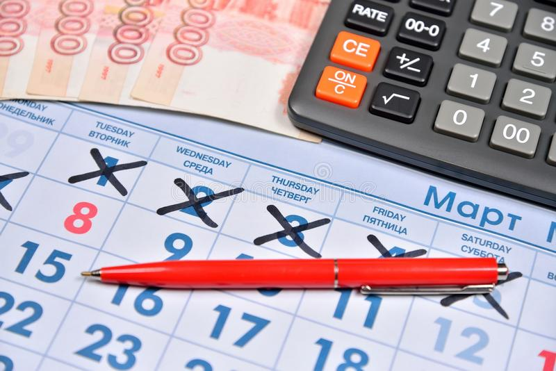 Electronic calculator, red pen and banknotes of five thousand ru. Bles are on the calendar with a holiday on March 8. Business still life stock image