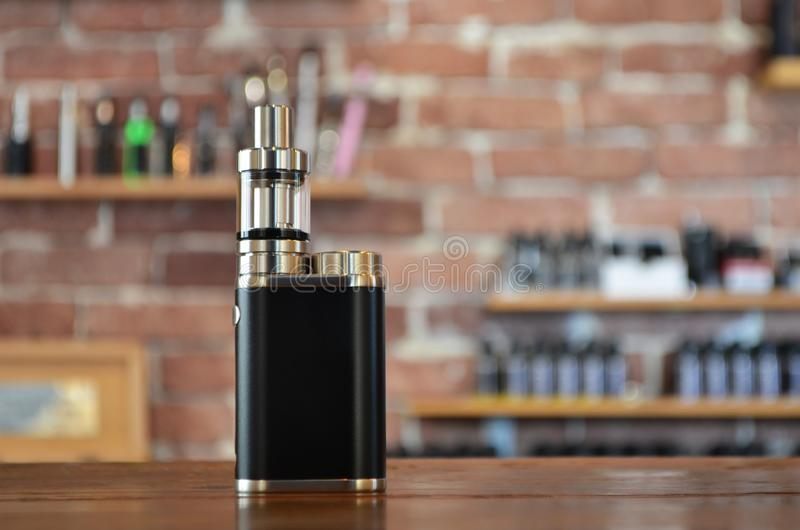 Electronic cigarette on a background of vape shop. E-cigarette for vaping. Popular vape devices royalty free stock photography
