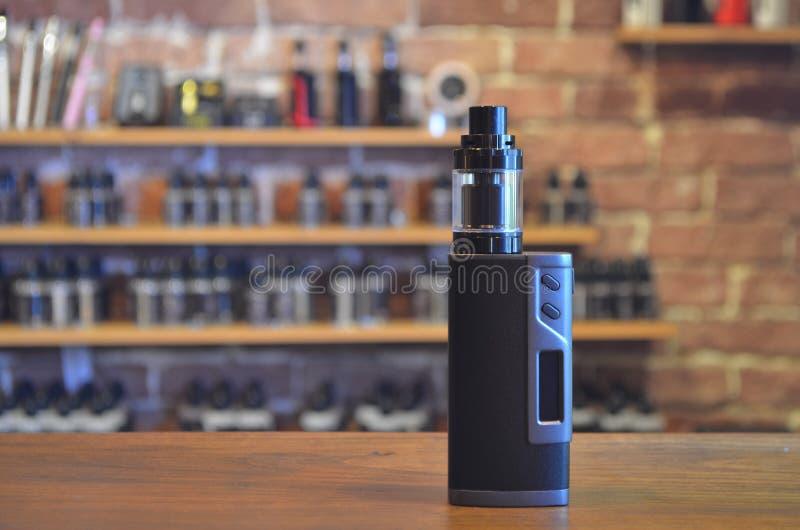 Electronic cigarette on a background of vape shop. E-cigarette for vaping. Popular vape devices stock photos
