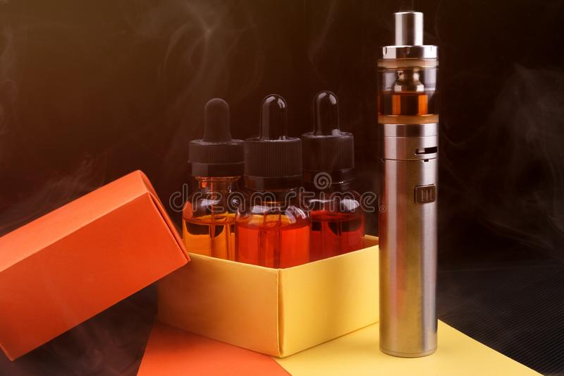 Electronic cigarette and vape liquids into opened gift box on fogged dark background. Toned light. Electronic cigarette and assorted vape liquids into opened stock image