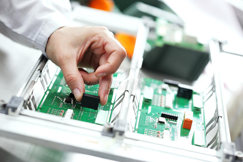 Electronic component assembly. Technician assembling electonic components at his worktable royalty free stock photo