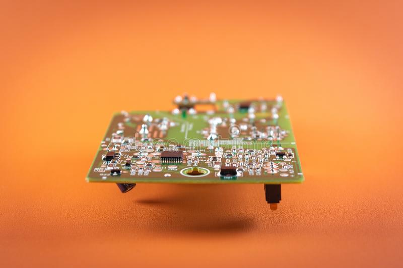 Electronic component. Green circuit board with chip and parts isolated on orange background royalty free stock photo
