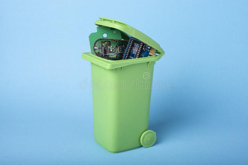 Electronic components in a green waste basket stock images