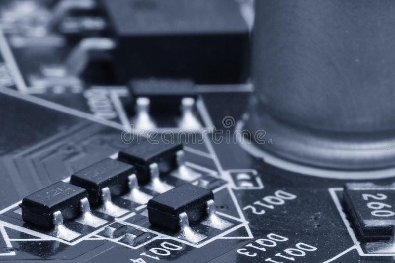 Electronic components are mounted on the device board Toned image. Electronic components are mounted on the device board Chips diodes capacitors chokes Toned stock images